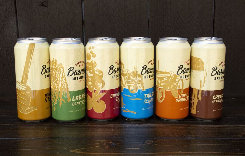 6 tall Barnside Brewing beer cans showing their core series, each containing a unique illustration and brand colour, sitting against a dark wooden background
