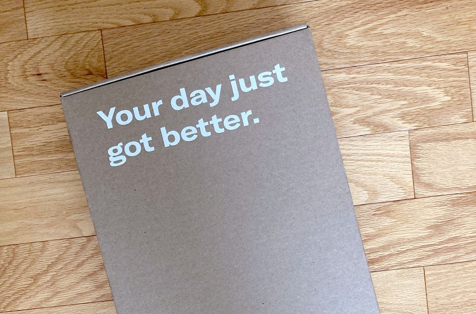 Grey box with white text on it reading 'your day just got better' sitting against a wooden panel background