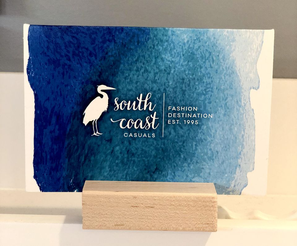 White gift card covered with a blue watercolour pattern and branded with South Coast Casuals logo printed on it sitting in a wooden block stand