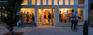 The front of a yoga studio, taken in the evening after sunset. The orange glow from the studio lights create a warm contrast against the evening sidewalk and tree. The large windows of the studio show a variety of people inside chatting as the class has ended