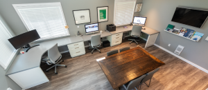 A room of a design studio, showing a combined desk with 3 computers, 3 grey office chairs, white drawers, and a center wooden table. Across the walls are a series of framed graphics and quotes, with a shelf on the right wall covered in printed pieces, created by the graphic design studio